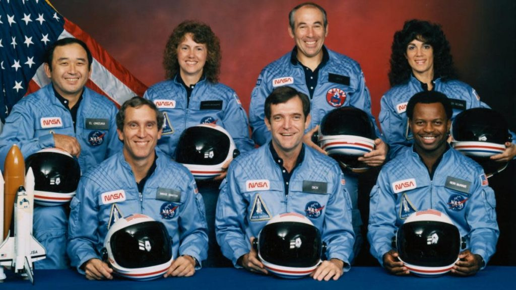 Пять астронавтов и два специалиста по полезной нагрузке, которые составили экипаж STS 51-L на борту космического челнока Challenger в январе 1986 года. Члены экипажа (слева направо, в первом ряду) астронавты Майкл Дж. Смит, Фрэнсис Р. (Дик) Скоби и Рональд Э. Макнейр; и Эллисон С. Онизука, Шэрон Криста МакОлифф, Грегори Джарвис и Джудит А. Резник.